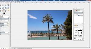 """1. Starten Sie GIMP und öffnen Sie das Foto, das Sie bearbeiten möchten. Wichtig: Die Aufnahme sollte einen hohen Himmelanteil mit einheitlicher Farbgebung aufweisen. Zusätzlich sollten mehrere Bildelemente in die Höhe ragen – in diesem Fall die Palmen und Bäume. Klicken Sie im Ebenen-Werkzeugkasten auf das Symbol für """"Ein Duplikat dieser Ebene erstellen."""